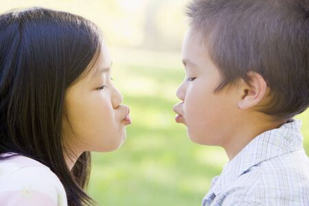 Brother and sister outdoors with eyes closed puckering up Stock Photo - 3487386