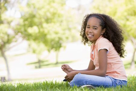 Young girl sitting outdoors smiling Stock Photo - 3486311