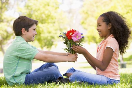 Young boy giving young girl flowers and smiling photo