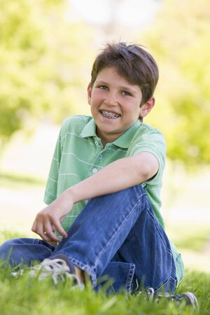 teeth braces: Young boy sitting outdoors smiling