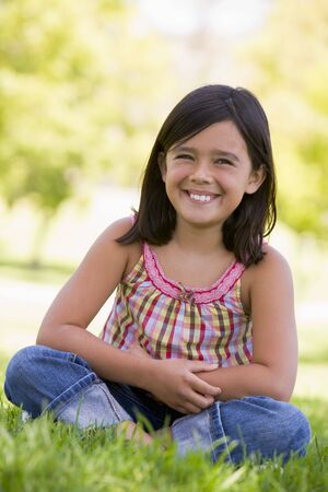 preadolescent: Young girl sitting outdoors smiling Stock Photo
