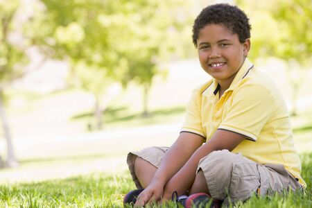 Young boy sitting outdoors smiling Stock Photo - 3486291
