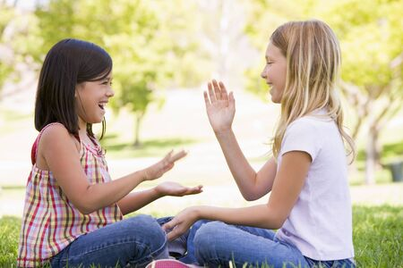 Two young girl friends sitting outdoors playing patty cake smiling Stock Photo - 3486802