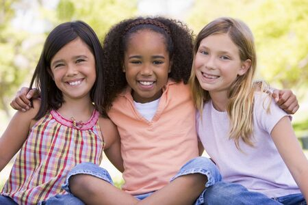 best friends girls: Three young girl friends sitting outdoors smiling Stock Photo