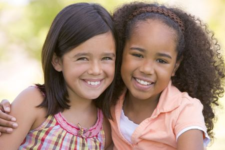 Two young girl friends sitting outdoors smiling Stock Photo - 3487926