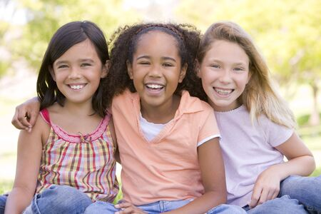 Three young girl friends sitting outdoors smiling photo