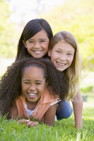 Three young girl friends piled up on top of each other outdoors smiling photo