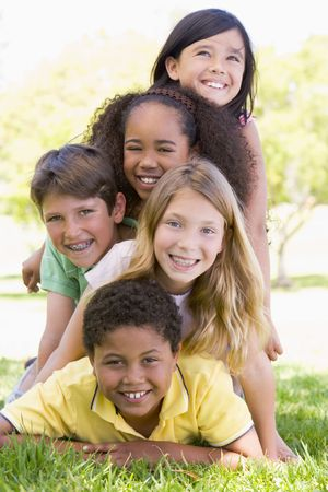heap up: Five young friends piled up on top of each other outdoors smiling