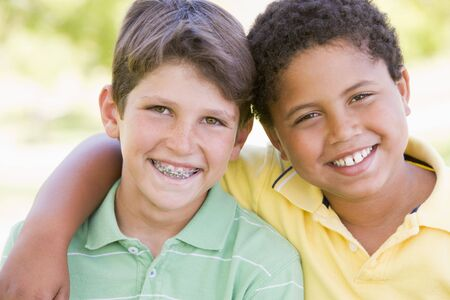 Two young male friends outdoors smiling photo