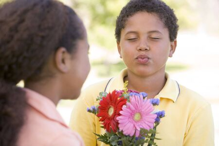 Young boy giving young girl flowers and puckering up Stock Photo - 3486335