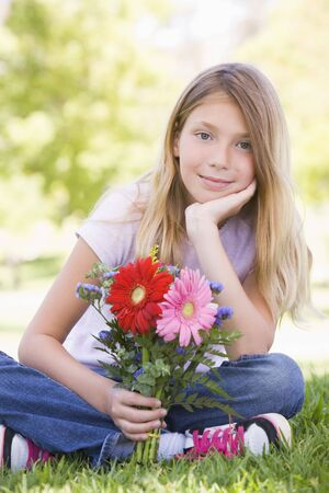 Young girl holding flowers and smiling photo
