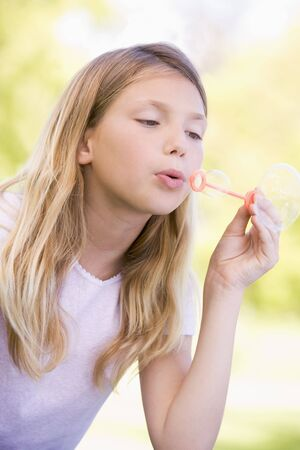 Young girl blowing bubbles outdoors photo