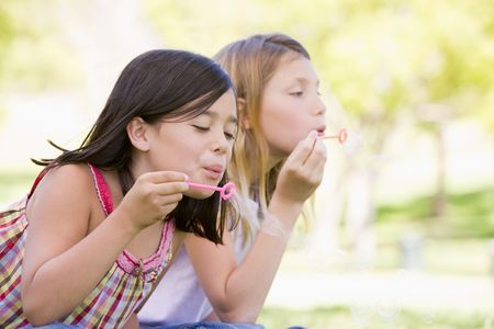 blowing bubbles: Two young girls blowing bubbles outdoors