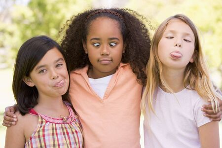 american children: Three young girl friends outdoors making funny faces Stock Photo