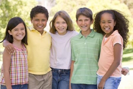 야외에서 웃 고 서있는 다섯 젊은 친구 스톡 콘텐츠