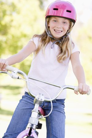 Young girl on bicycle outdoors smiling Stock Photo - 3487431