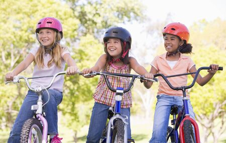 Three young girl friends outdoors on bicycles smiling photo