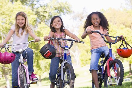 riding helmet: Three young girl friends outdoors on bicycles smiling