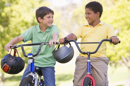 Two young boys on bicycles outdoors smiling photo