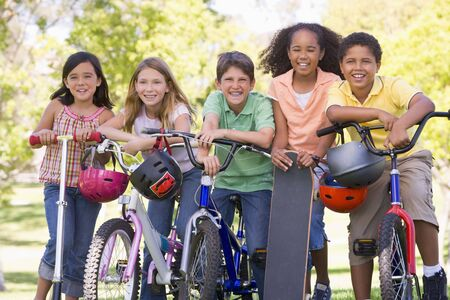 Five young friends with bicycles scooters and skateboard outdoors smiling photo