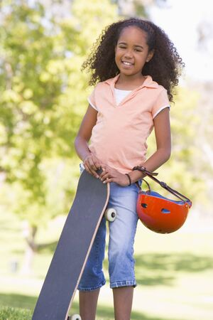 Young girl with skateboard outdoors smiling Stock Photo - 3486788