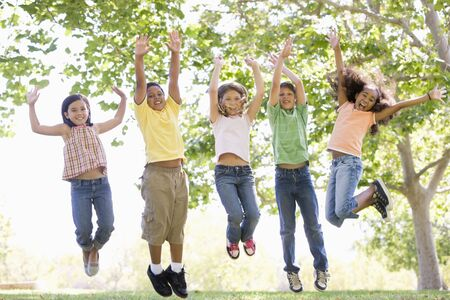 latinos: Five young friends jumping outdoors smiling