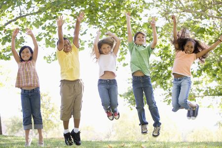 Five young friends jumping outdoors smiling photo