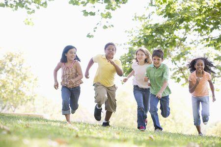 nina corriendo: Cinco jóvenes amigos al aire libre, corriendo sonriente