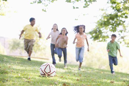 ni�as jugando: Cinco j�venes amigos jugando al f�tbol Foto de archivo