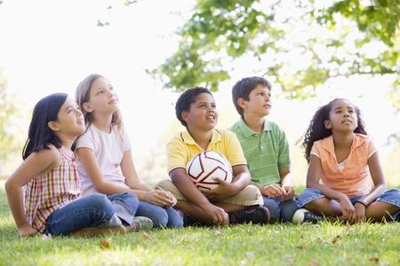 Five young friends sitting outdoors with soccer ball looking up photo
