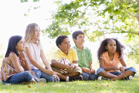 multi racial groups: Five young friends sitting outdoors with soccer ball