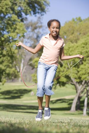 leaping: Young girl using skipping rope outdoors smiling