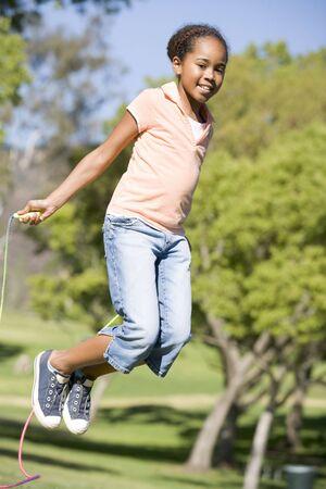 saltar la cuerda: Jovencita usando saltar la soga al aire libre sonriente