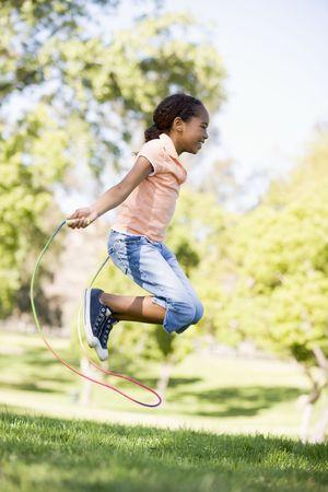 saltar la cuerda: Ni�a saltando la cuerda al aire libre utilizando sonriente
