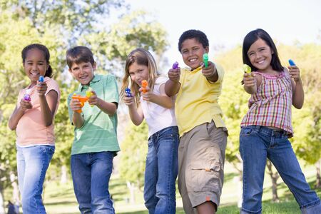 Five young friends with water guns outdoors smiling photo