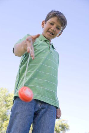 yo: Young boy using yo yo outdoors smiling
