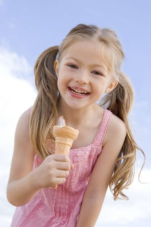 ice cream cone: Young girl outdoors eating ice cream cone and smiling