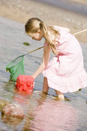 Young girl at beach with net and pail photo