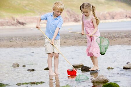 discovering: Brother and sister at beach with nets and pail