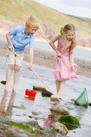 Brother and sister at beach with nets and pail photo