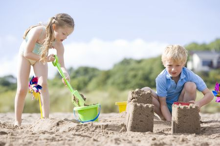Brother and sister at beach making sand castles photo