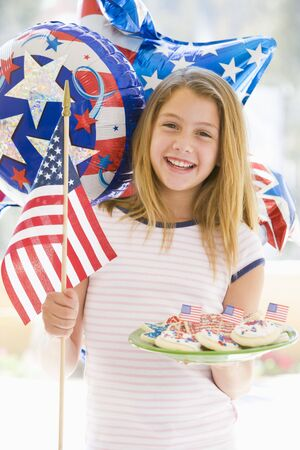 independence day: Young girl outdoors on fourth of July with flag and cookies smiling