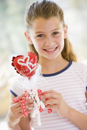 Young girl on Valentines Day holding love themed balloon smiling photo