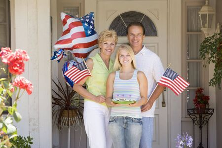 Family at front door on fourth of July with flags and cookies smiling Фото со стока