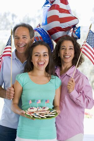 Family outdoors on fourth of July with flags and cookies smiling Stock Photo - 3488098
