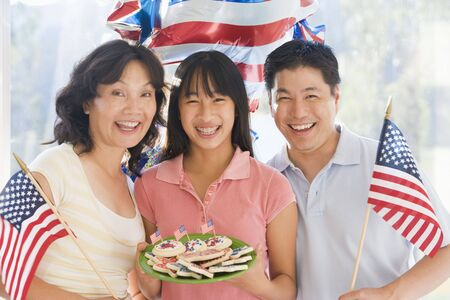 Family outdoors on fourth of July with flags and cookies smiling photo