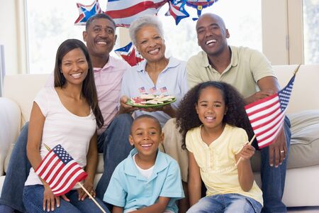 african america: Family in living room on fourth of July with flags and cookies smiling
