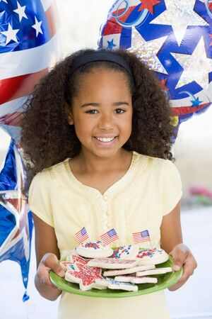 Young girl on fourth of July with balloons and cookies smiling photo