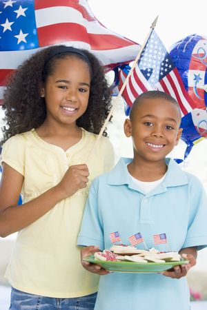 Brother and sister on fourth of July with flag and cookies smiling photo
