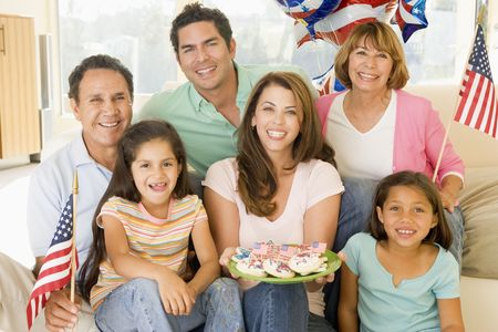 Family in living room on fourth of July with flags and cookies smiling photo